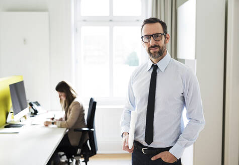 Portrait of confident businessman in office with employee in background - MIKF00020