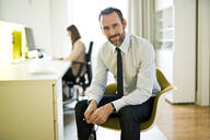 Portrait of confident businessman in office with employee in background - MIKF00026