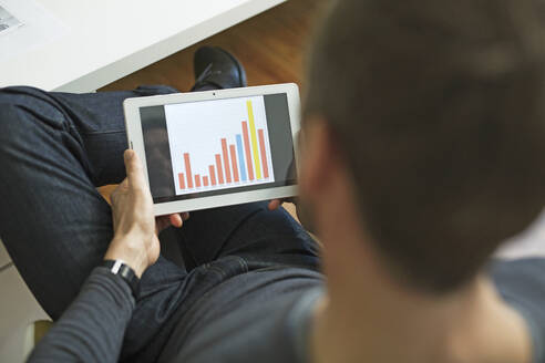 Businessman analyzing bar chart on tablet in office - MIK00047