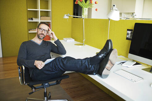 Portrait of smiling businessman in office with feet on desk - MIK00050
