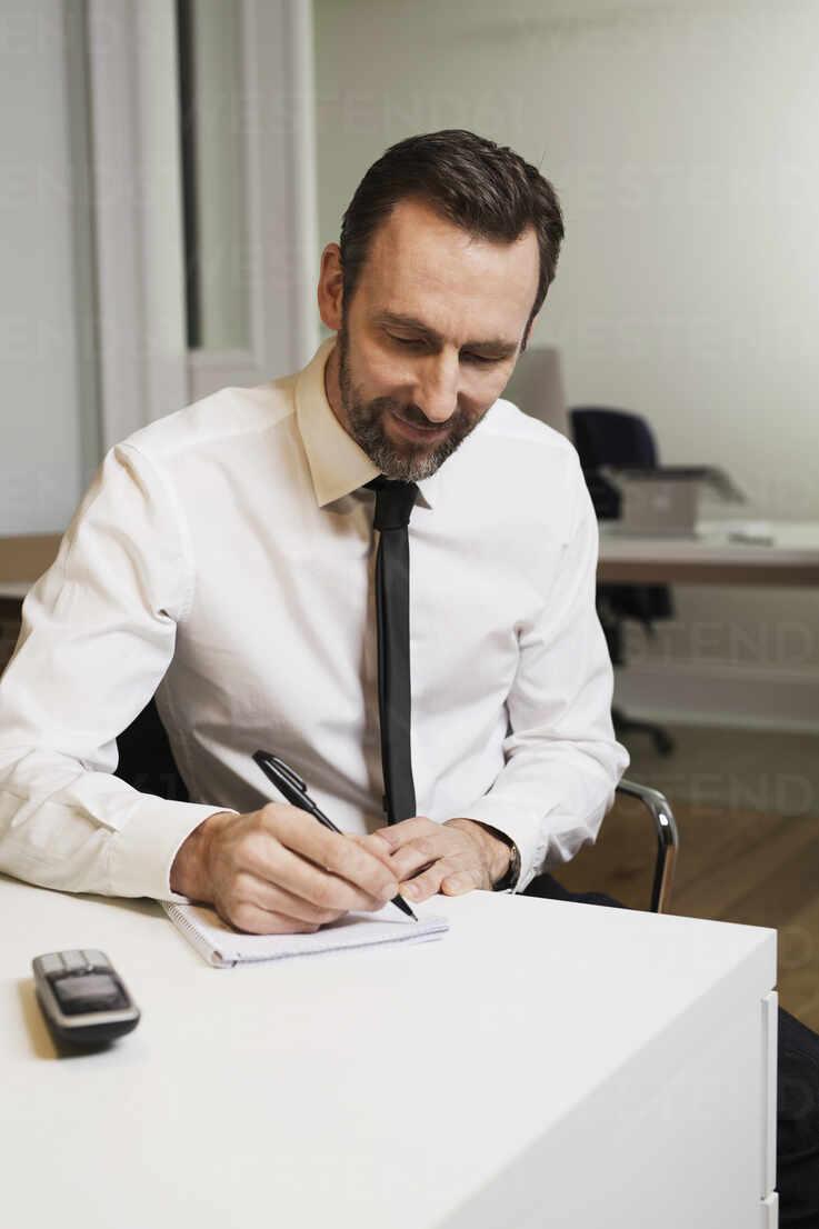 Businessman sitting at desk in office taking notes - MIK00056 - Fritz Miller/Westend61