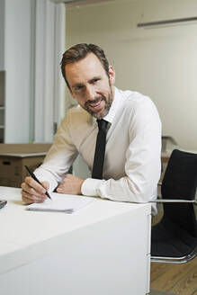 Portrait of confident businessman sitting at desk in office taking notes - MIK00059
