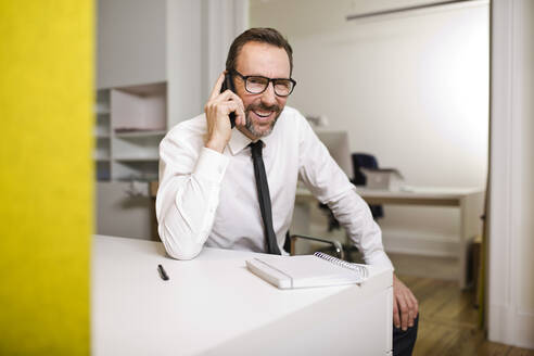Businessman talking on the phone at desk in office - MIK00062