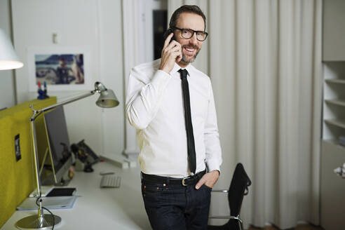 Smiling businessman talking on the phone in office - MIK00065