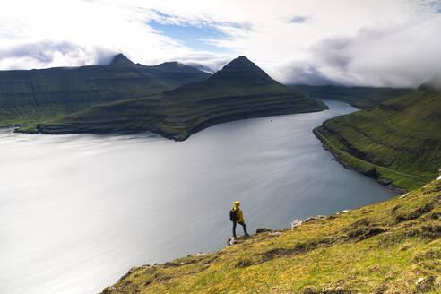 Hiker on rocks looks at the fjords, Funningur, Eysturoy island, Faroe Islands, Denmark, Europe - RHPLF12098