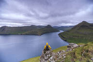 Hiker sitting on rocks looking at the fjords, Funningur, Eysturoy island, Faroe Islands, Denmark, Europe - RHPLF12101