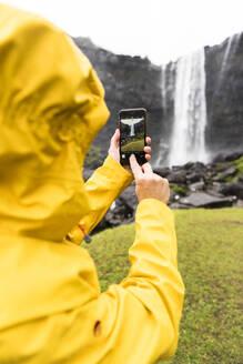 Tourist snaps photos with smartphone, Fossa waterfall, Streymoy island, Faroe Islands, Denmark, Europe - RHPLF12116
