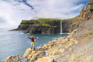 Man on cliffs with open arms admiring Gasadalur waterfall, Vagar island, Faroe Islands, Denmark, Europe - RHPLF12128