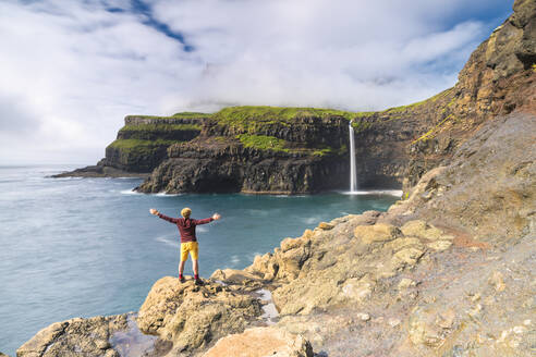 Man on cliffs with open arms admiring Gasadalur waterfall, Vagar island, Faroe Islands, Denmark, Europe - RHPLF12128