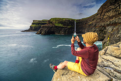 Man with smartphone snaps photos at Gasadalur waterfall, Vagar island, Faroe Islands, Denmark, Europe - RHPLF12131