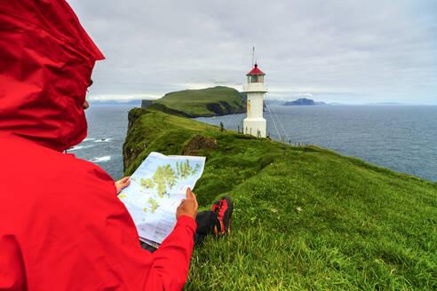 Hiker on cliffs looks at the map next to lighthouse, Mykines island, Faroe Islands, Denmark, Europe - RHPLF12134