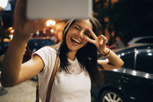Young woman using smartphone in the city at night, taking a selfie - OYF00082