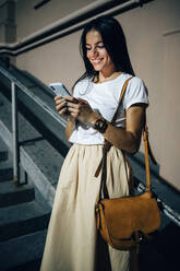 Young woman using smartphone in the city at night - OYF00085