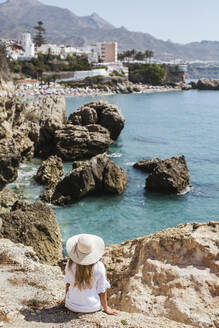 Back view of woman wearing white dress and straw hat sitting on rocks looking to the sea, Nerja, Spain - LJF00994
