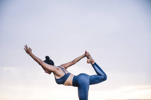Woman practicing yoga, dancer position - OCMF00733