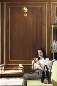 Businesswoman using cell phone in a restaurant - JSRF00604