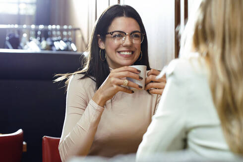 Portrait of a smiling woman with friend in a cafe - JSRF00607