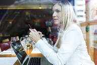 Businesswoman using laptop and cell phone in a restaurant - JSRF00619