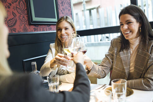 Smiling businesswomen meeting and clinking wine glasses in a restaurant - JSRF00625
