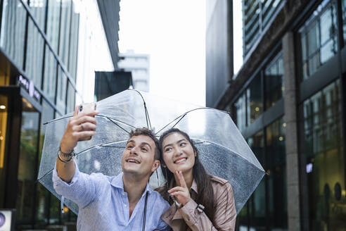 Happy couple with umbrella taking a selfie in Ginza, Tokyo, Japan - MCVF00026