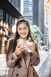 Happy young woman holding takeaway drink and using smartphone in Ginza, Tokyo, Japan - MCVF00029