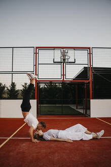 Young couple on a basketball ground, woman lying and man doin a handstand and kissing her - LHPF00883
