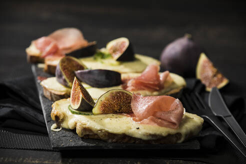 Close-up of baked cheese bread with fig and ham served on table - MAEF12946