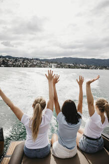 Cheerful female friends on a boat trip on a lake - LHPF00892