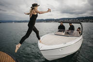 Young woman jumping on a boat on a lake - LHPF00922