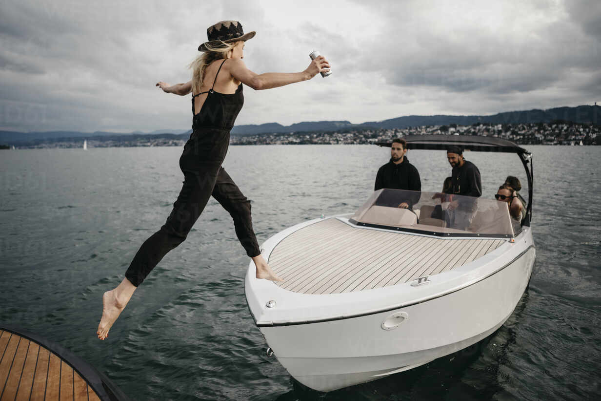 Young woman jumping on a boat on a lake - LHPF00922 - letizia haessig photography/Westend61