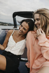 Happy female friends on a boat trip on a lake - LHPF00928