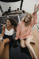 Happy friends on a boat trip on a lake - LHPF00931