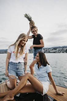 Happy female friends having fun on a boat trip on a lake - LHPF00946