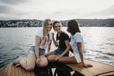 Happy female friends having fun on a boat trip on a lake - LHPF00949