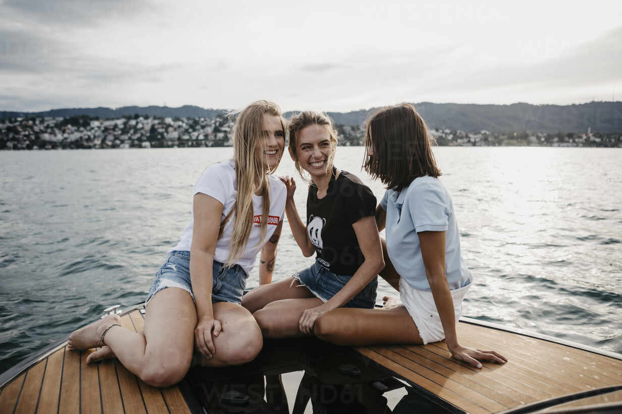Happy female friends having fun on a boat trip on a lake - LHPF00949 - letizia haessig photography/Westend61