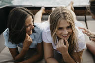 Happy female friends relaxing on a boat - LHPF00955