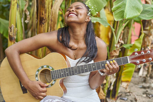 Happy woman playing guitar outdoors - VEGF00717