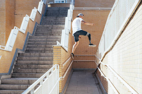 Young man with leg prosthesis performing parkour in the city - JCMF00222