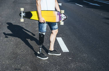 Young man with leg prosthesis holding skateboard on a road - JCMF00228