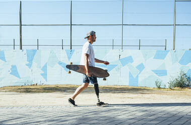 Young man with leg prosthesis walking and holding skateboard - JCMF00231