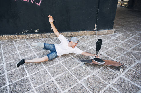 Young male crazy with leg prosthesis smiling away while holding skateboard - JCMF00240