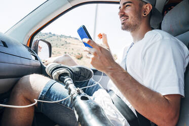Smiling young man with leg prosthesis sitting in camper van using smartphone - JCMF00243