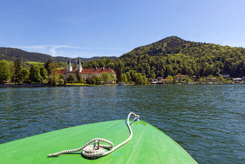 Boat on lake with Tegernsee Abbey and St. Quirinus Church in background against blue sky in Bavaria, Germany - LHF00720
