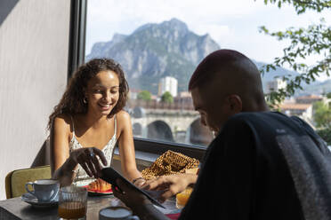 Young couple in a coffee shop looking at smartphone during breakfast, Lecco, Italy - MCVF00040