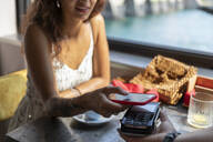 Young woman paying bill with smartphone at coffee shop - MCVF00043