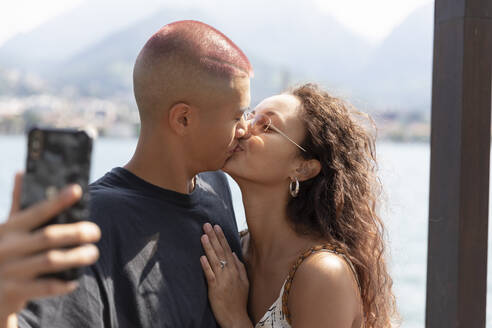 Young couple taking selfie with cell phone while kissing, Lecco, Italy - MCVF00046