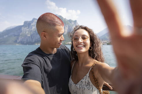 Young couple taking selfie in front of Lake Como, Lecco, Italy - MCVF00049