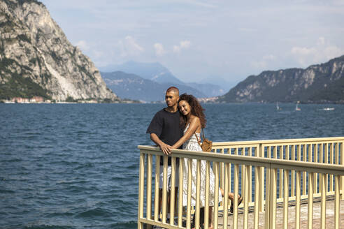 Happy young couple standing on terrace in front of Lake Como, Lecco, Italy - MCVF00055