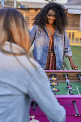Portrait of young woman playing table football with her friend - VEGF00721