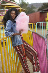 Portrait of smiling young woman with pink candyfloss at fair - VEGF00730